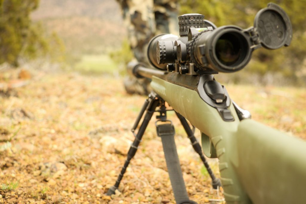 A green hunting rifle with scope stabilized on the ground with a bipod. Image taken from right-handed shooter view.